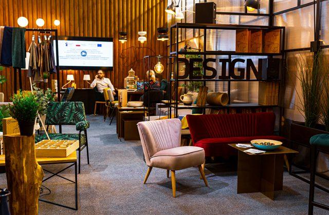 stoisko Customform z eleganckim różowym fotelem obok niedużej czerwonej sofy z przeszyciami bez oparć