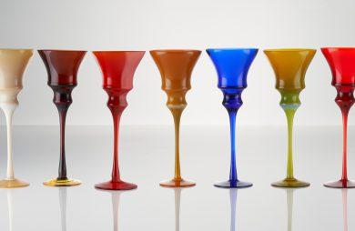 zestaw szklanych kolorowych małych kieliszków na wysokiej nóżce