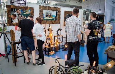 cztery osoby oglądających stoisko z nietypowymi dekoracjami wnętrza