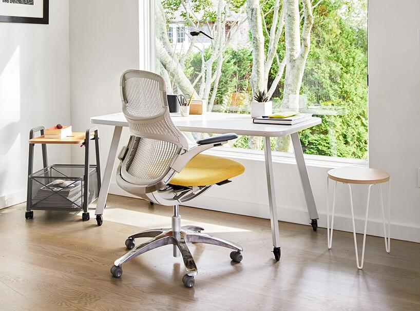 białe biurko na kółkach znowoczesnym krzesłem zżółtym siedziskiem na tle dużego okna zwidokiem na drzewo