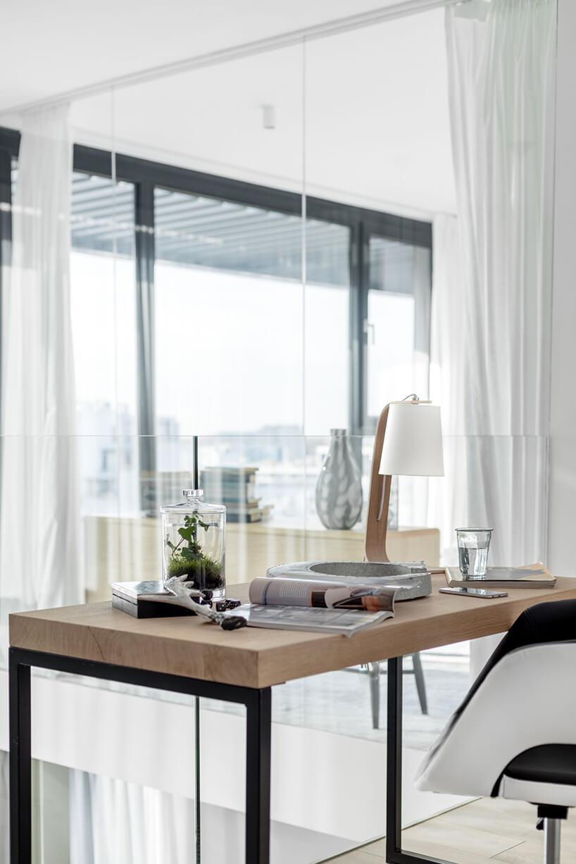 eleganckie biurko na metalowych nogach zgrubym drewnianym blatem zbiało czarnym krzesłem