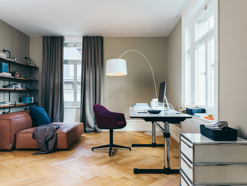 nowoczesne biurko zregulacją wysokości na chromowanych nogach zbiałym blatem na drewnianym parkiecie zczarnym krzesła zfioletowym siedziskiem