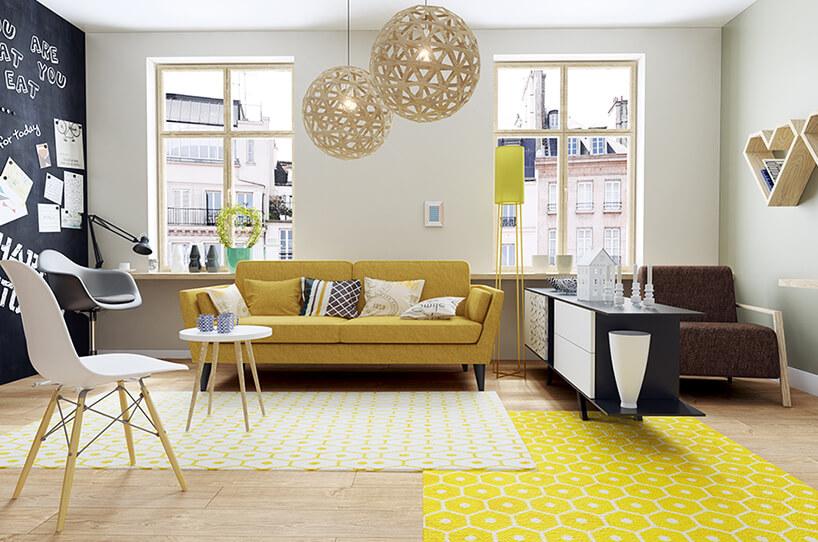 nowoczesne wnętrze zdwoma jasnymi dywanami jedną ciemną ścianą wformie tablicy iżółta sofa