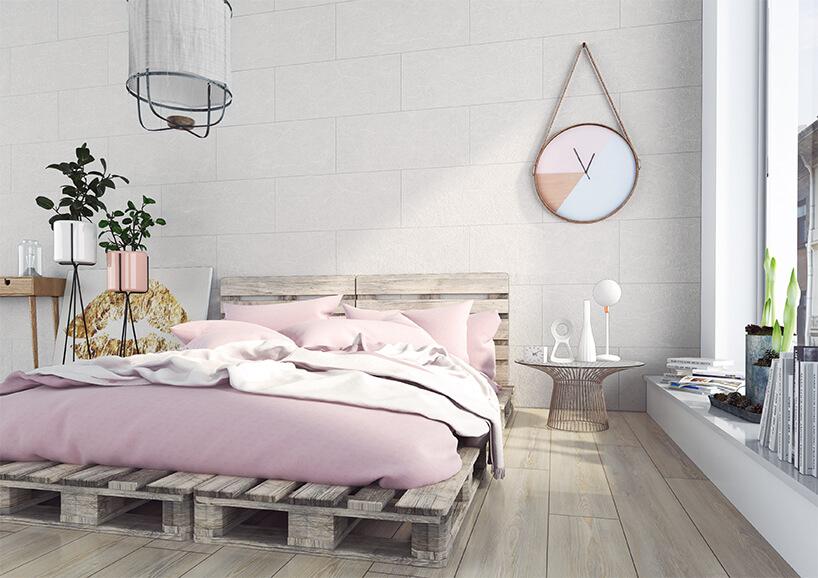nowoczesna sypialnia zdużym łóżkiem na paletach zdużym zegarem zawieszonym na sznurku