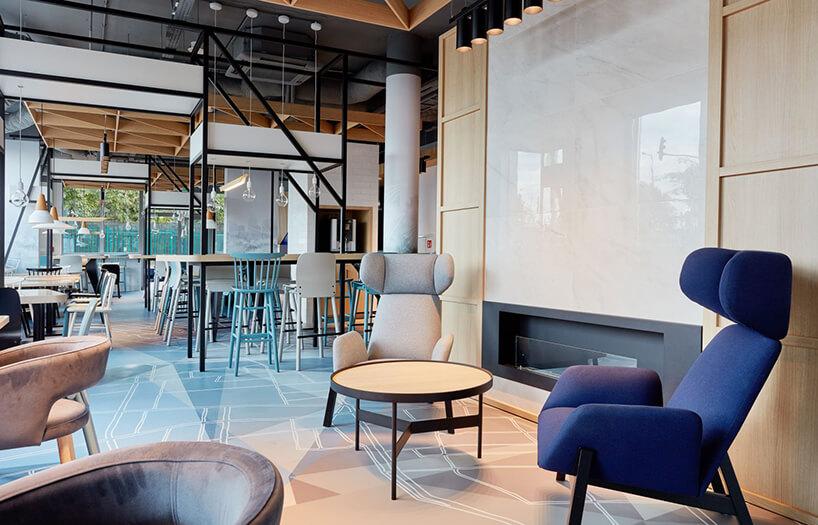 szary iniebieski fotel przy czarnym niskim stoliku zdrewnianym blatem na tle drewnianej ścianie