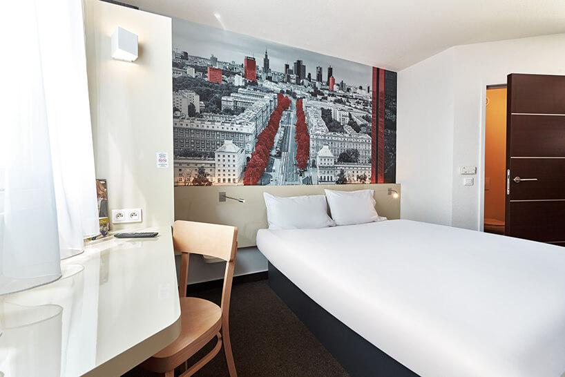 jasne wnętrze pokoju hotelowego duże łóżko na tle zdjęcia Warszawy