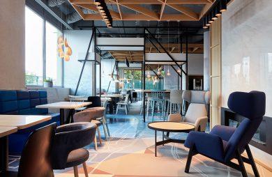 szary i niebieski fotel przy czarnym niskim stoliku z drewnianym blatem