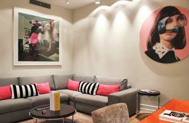 wnętrze hotelu H15 w Warszawie z szarą sofą i pomarańczowym stolikiem