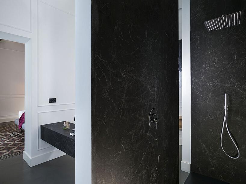 spieki kwarcowy Laminam whotelu Habitat elegancki natrysk zczarną ścianą na tle białych ścian wpozostałej części łązienki