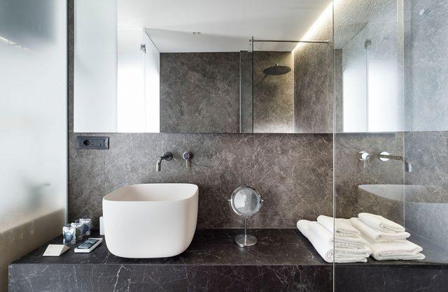 spieki kwarcowy Laminam w hotelu Habitat ciemna łazienka z czarnym blatem