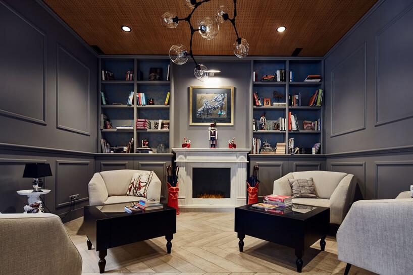 dwa fotele ze stolikami na tle szarych ścian