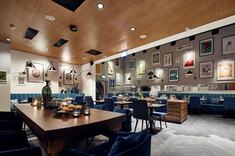 duże brązowe drewniane stoły zniebieskimi krzesłami wczęści restauracyjnej hotelu Indigo