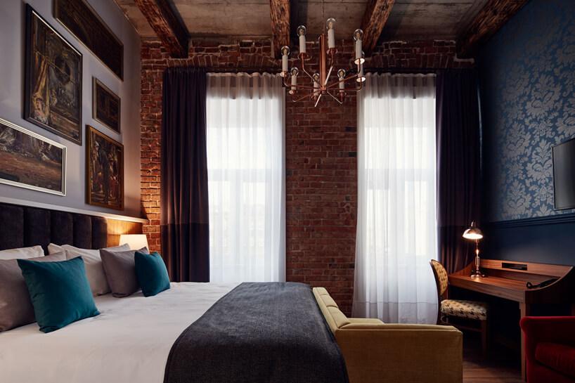 pokój hotelowy zdużymi łóżkiem ibiurkiem na tle ściany zcegieł idrewnianego sufitu