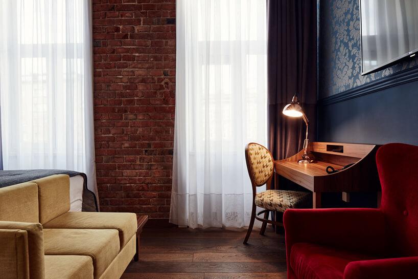 wnętrze wstarym stylu zmałym drewnianym biurkiem krzesłem iczerwonym fotelem