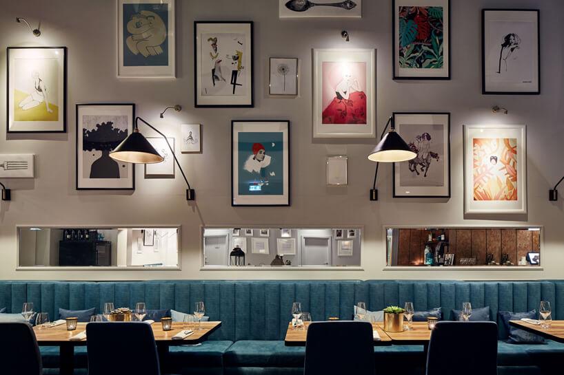 część restauracyjna na tle ściany zdużą liczbą obrazów