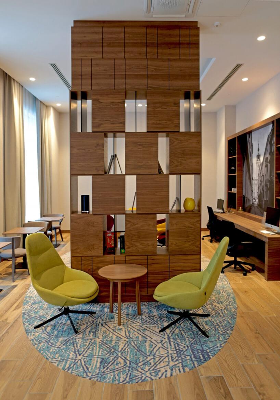 wnętrze hotelu Hampton by Hilton Kalisz wCalisia One dwa zielone krzesła przy małym stoliku