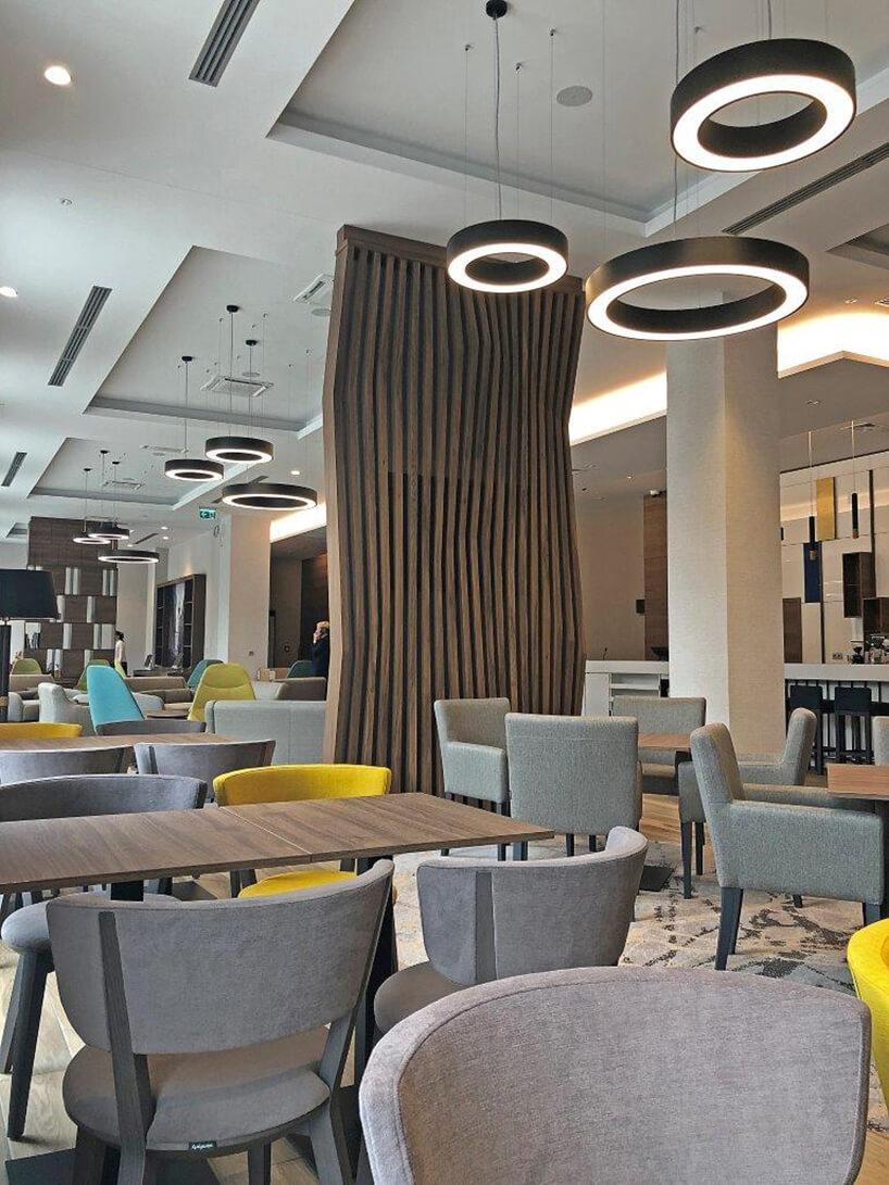 wnętrze hotelu Hampton by Hilton Kalisz wCalisia One jadalnia zszarymi krzesłami idrewnianymi stołami