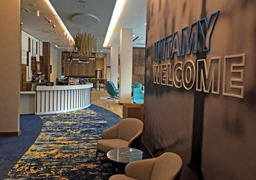 wnętrze hotelu Hampton by Hilton Kalisz wCalisia One napis na ścianie nad dwoma brązowymi krzesłami