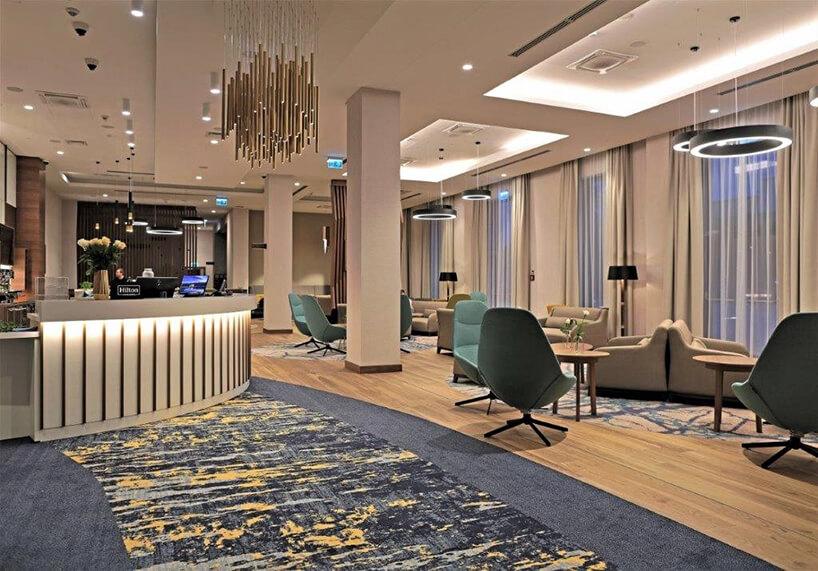 wnętrze hotelu Hampton by Hilton Kalisz wCalisia One krzesła istoły przy recepcji