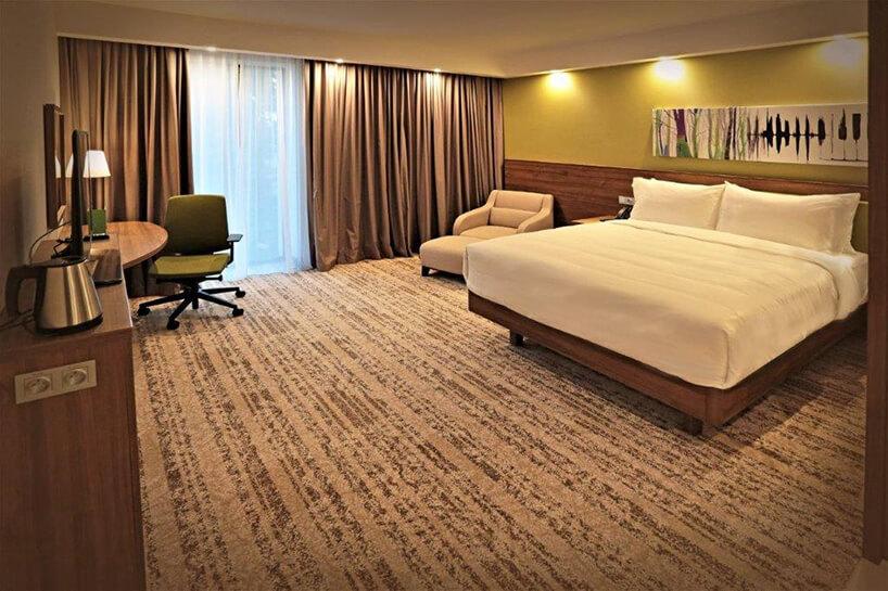 wnętrze hotelu Hampton by Hilton Kalisz wCalisia One przestronny pokój zdużym łóżkiem krzesłem obrotowym ileżanką