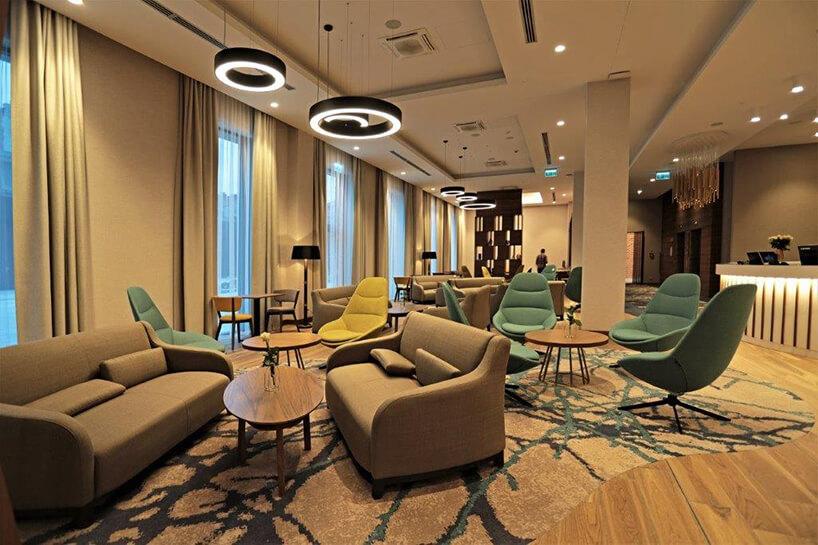 wnętrze hotelu Hampton by Hilton Kalisz wCalisia One sofy krzesła istoliki przed recepcją