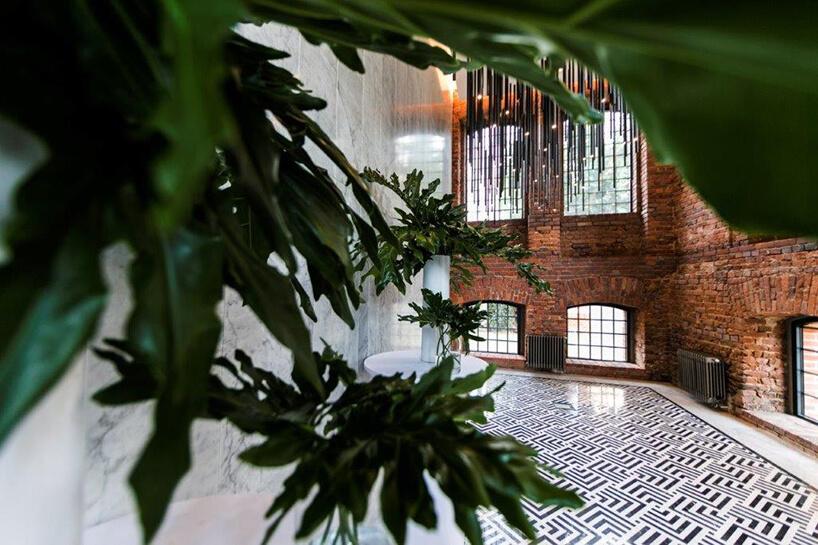 wnętrze hotelu Hampton by Hilton Kalisz wCalisia Onebiało czarna podłoga wholu zceglanymi ścianami