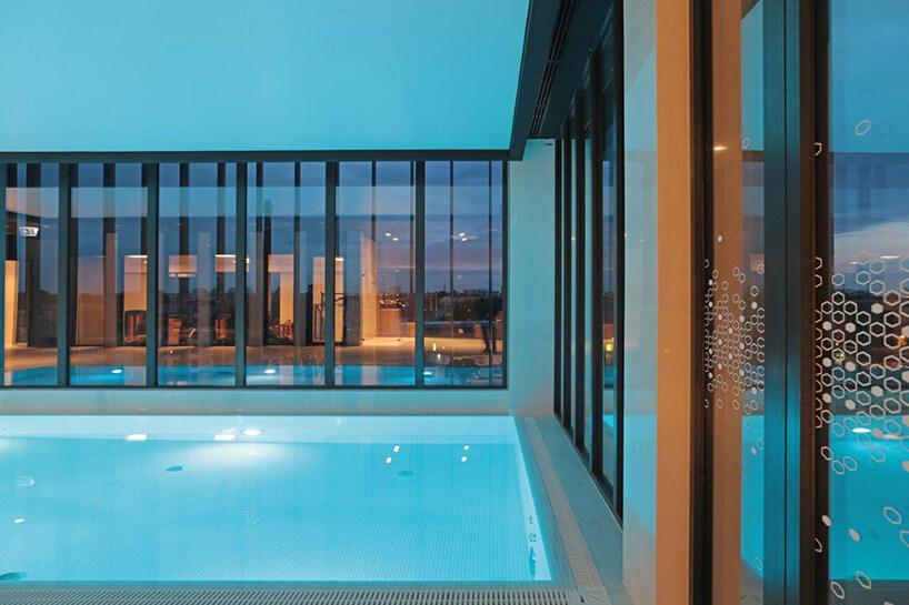 wnętrze hotelu Hampton by Hilton Kalisz wCalisia One zewnętrzny basen na tle przeszklonych ścian hotelu