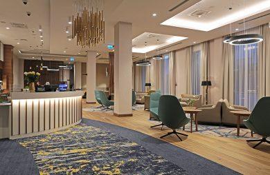wnętrze hotelu Hampton by Hilton Kalisz w Calisia One krzesła i stoły przy recepcji