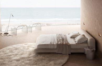 wyjątkowy pokój hotelowy duże beżowe łóżko na tle zaokrąglonego okna z widokiem na morze