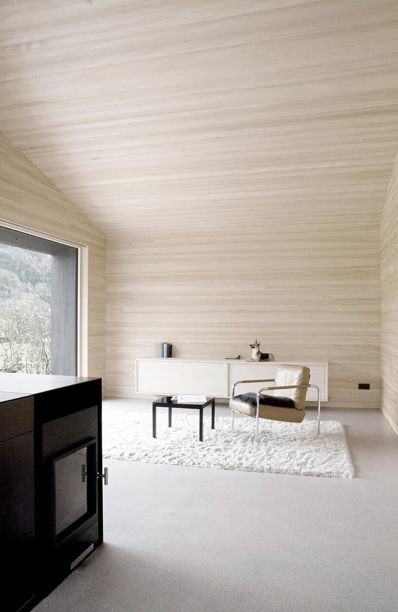 beżowy fotel zciemną poduszką stojący na białym dywanie