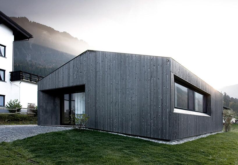 szary nowoczesny dom na zielonej trawie wgórach
