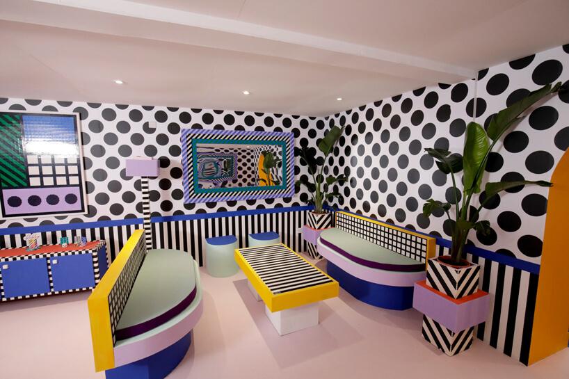 wnętrze instalacji House of Dots od Camille Walala kolorowa jadalnia zżółtym stołem zbiało czarnymi paskami na blacie