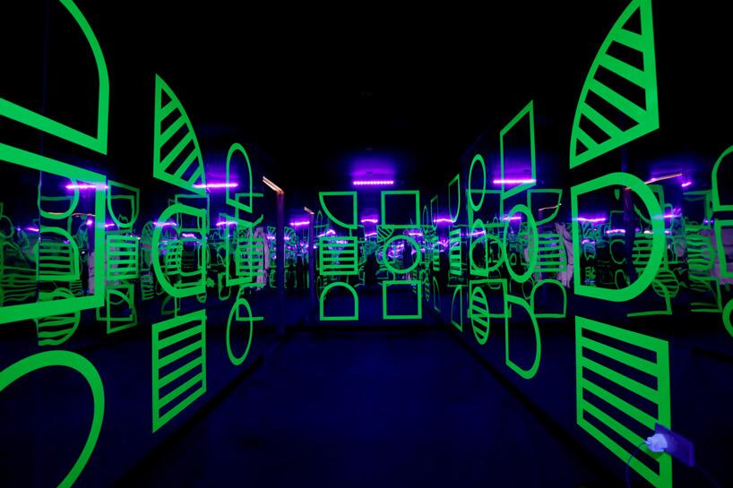 wnętrze instalacji House of Dots od Camille Walala ciemne pomieszczenie zzielonymi elementami na ścianach ifioletowym oświetleniem