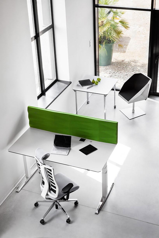 białe biurko wopen space zzieloną ścianką za blatem