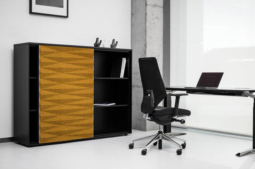 czarne biurko ikrzesło biurowe wgabinecie obok czarnej szafki zżółtym frontem