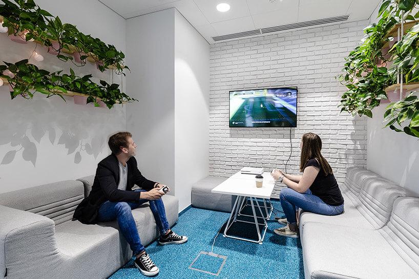 dwie osoby grające na konsoli wbiałym pomieszczeniu zniebieską podłogą