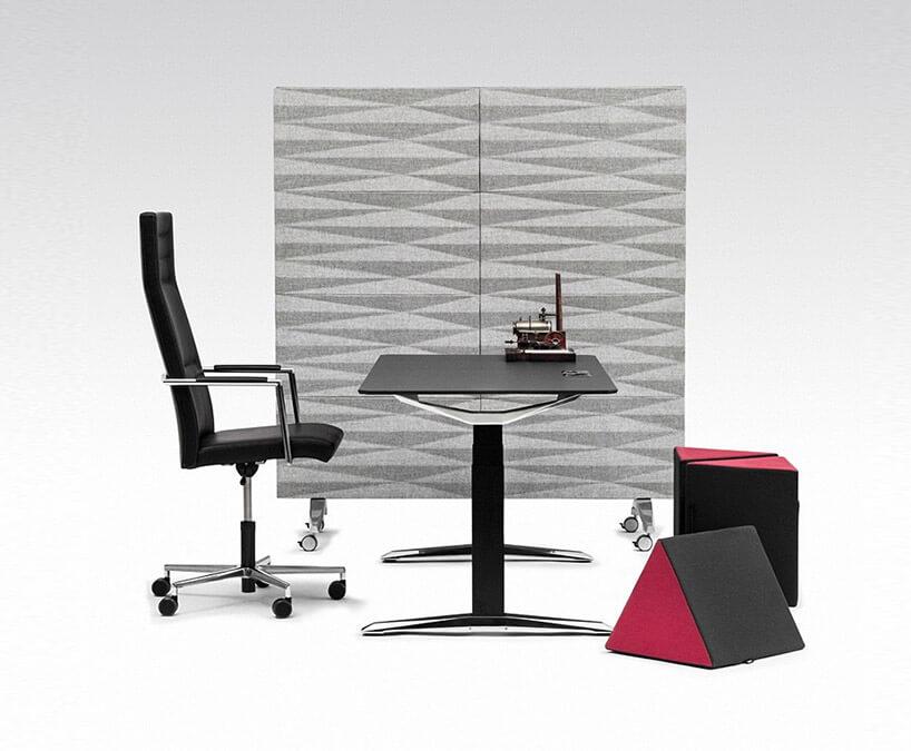 czarne biurko ikrzesło na tle szarej ścianki zkółkami