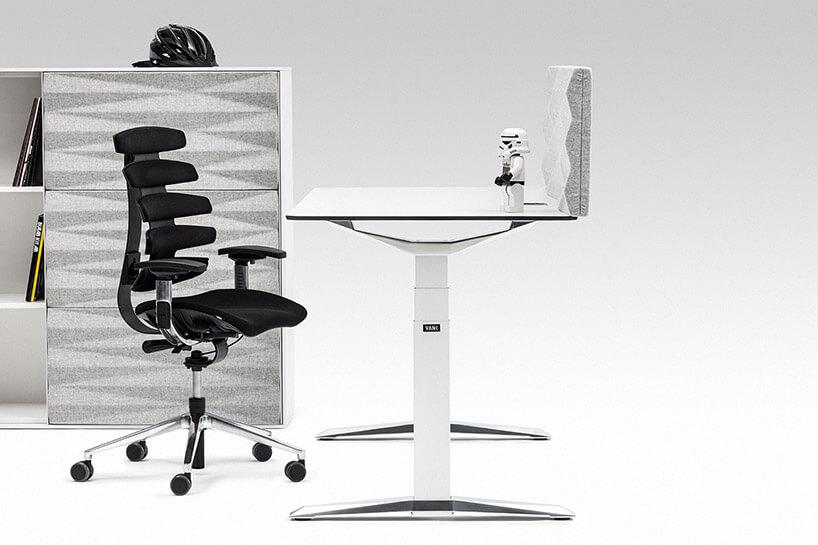 białe biurko zregulacją iczarne krzesło na tle szafki zszarym frontem