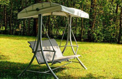 beżowa huśtawka ogrodowa z daszkiem na szarej metalowej konstrukcji
