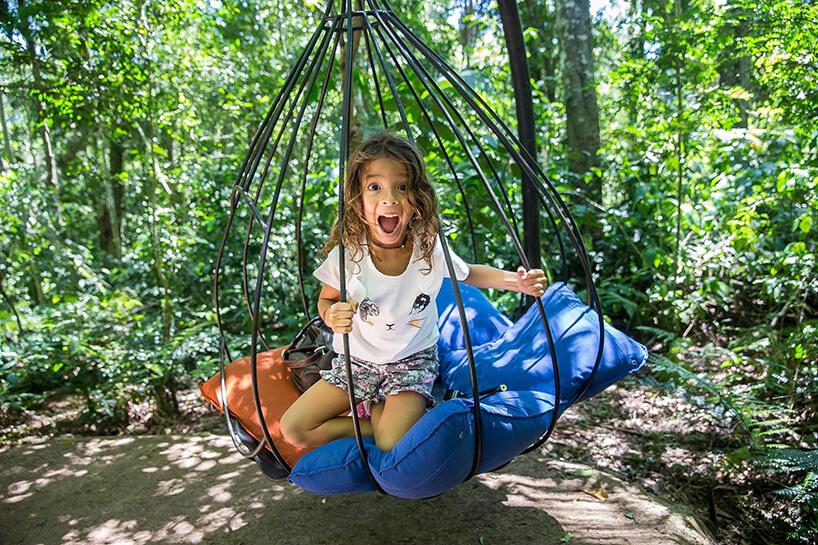 dziewczynka whuśtawce dla dzieci wogrodzie pełnym drzew