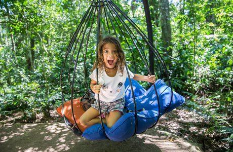 dziewczynka w huśtawce dla dzieci w ogrodzie pełnym drzew