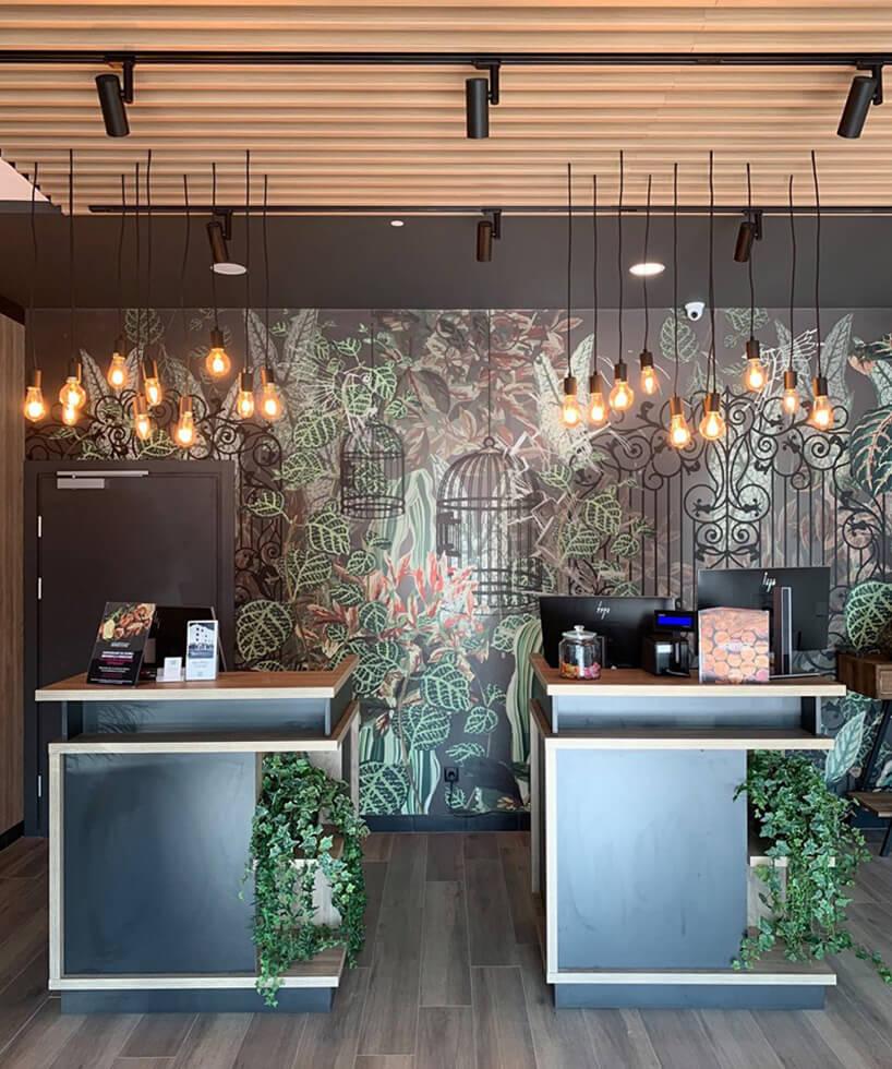 wnętrze hotelu ibis Styles Kraków od Accor rejestracja hotelowa na tle grafiki zmotywem roślinnym