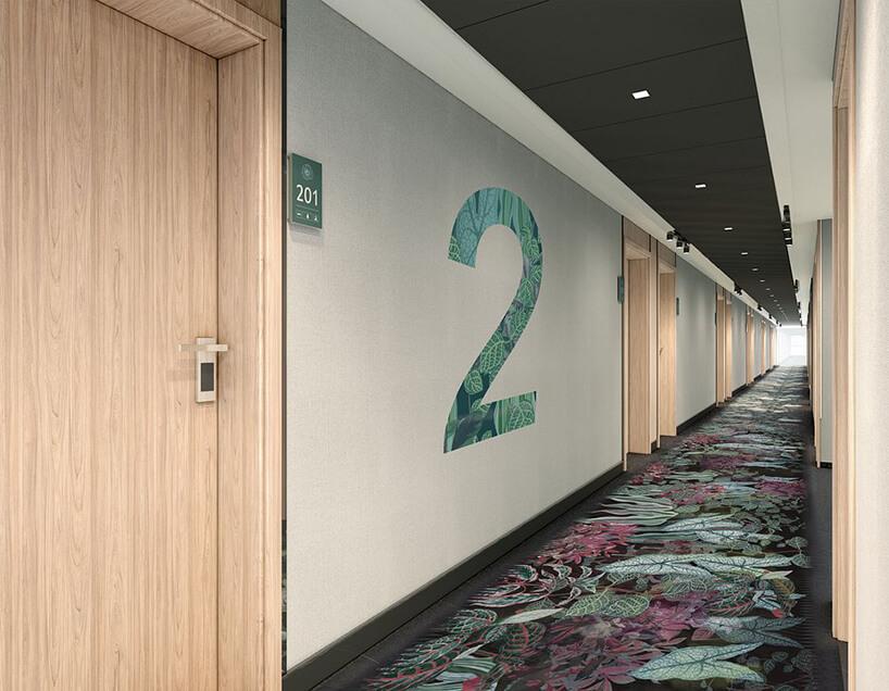 wnętrze hotelu ibis Styles Kraków od Accor hol zzjasnymi brązowymi drzwiami zwykładziną zmotywem roślinnym