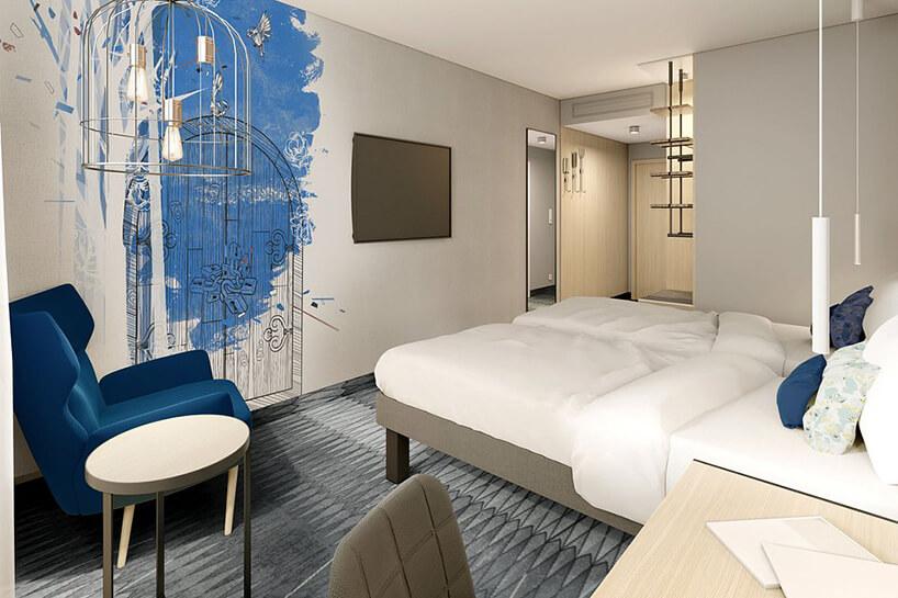 wnętrze hotelu ibis Styles Kraków od Accor jasne wnętrze pokoju zczarno niebieską grafika na ścianie zszarą wykładziną