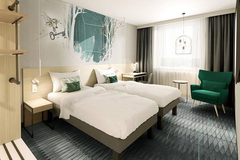 wnętrze hotelu ibis Styles Kraków od Accor jasne wnętrze wpokoju zdwoma łóżkami zzieloną grafiką na ścianie izielonym fotelem