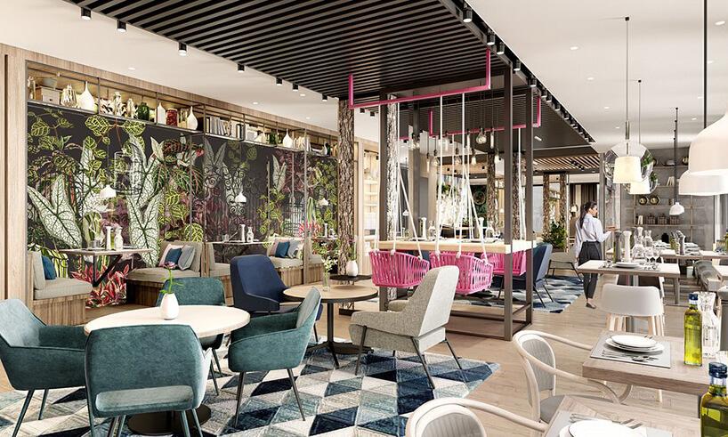 wnętrze hotelu ibis Styles Kraków od Accor przestrzeń jadalna wpastelowych kolorach ze stolikiem zróżowymi wiszącymi krzesłami