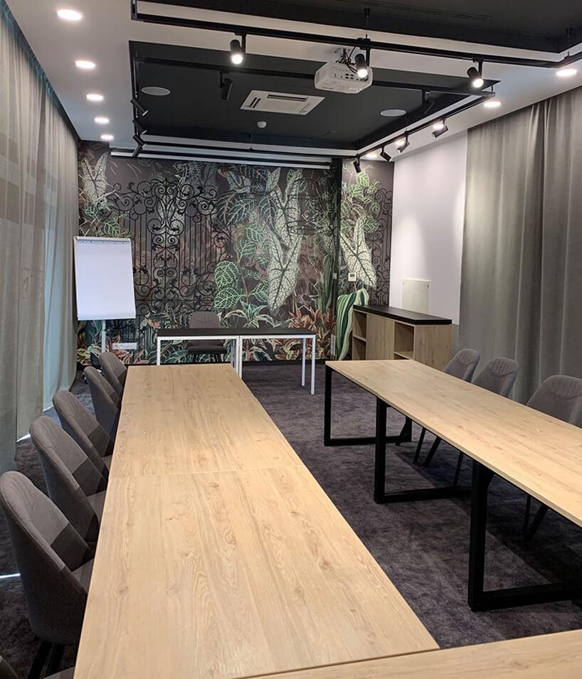 wnętrze hotelu ibis Styles Kraków od Accor mała sala konferencyjna zszarymi krzesłami zgrafiką zmotywem roslinnymi