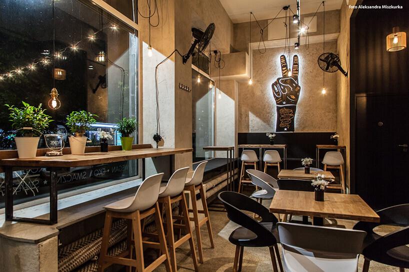 beżowo-czarne wnętrze restauracji ze zwisającymi kablami od oświetlenia