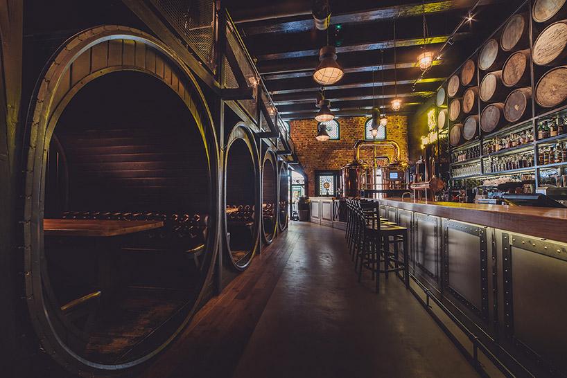 ciemne wnętrze restauracji ze stolikami wstarych wielkich beczkach