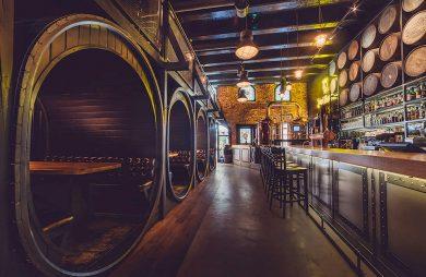 ciemne wnętrze restauracji ze stolikami w starych wielkich beczkach